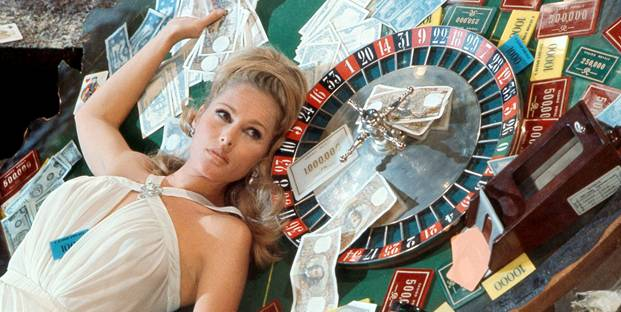 picture of blonde woman laying down on a casino table with money around her on a casino movie