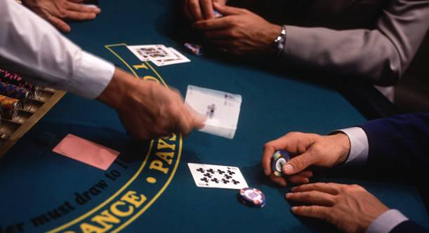 two men playing 21 blackjack with casino chips on the table and croupier handing out cards