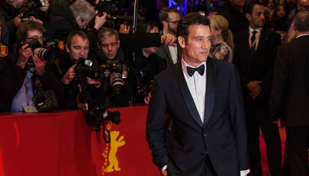 Clive Owen from croupier posing with photographers in the background on red carpet